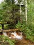Old chapel by a stream in the forest. The old chapel stands in the forest. By a flowing stream with clean, clear water royalty free stock images