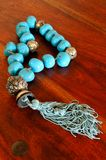 Old chaplet with turquoise beads. Picture of an old chaplet with large turquoise beads on a wooden table Royalty Free Stock Photo