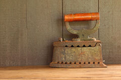 Old charcoal Iron on wooden table with wooden background Stock Photo