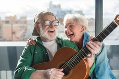 Old charming couple with guitar expressing joyfulness and pleasure. Endless sunshine. Waist up portrait of laughing aged men and women enjoying time together Stock Images