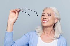 Old, charming, pretty woman looking through eyeglasses, senior, stock photos