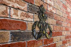 An old, chased monogram on a brick wall extending at an angle. Old chased monogram, poppy flower, against the background of a red brick wall stock photo