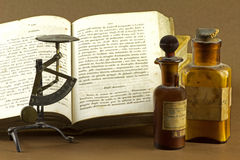 The old chemical laboratory. Old chemical book, scales and small bottles Stock Image
