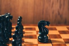 Old chess black knight standing ahead of the black chess pieces. Old chess - black knight standing ahead of the black chess pieces. Leader concept Royalty Free Stock Photography