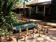 Old chess pieces by bench. Old chess pieces on table in the shade by a bench and home Royalty Free Stock Photography