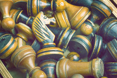 Old chess pieces. Many old wooden chess pieces with focus on black knight Royalty Free Stock Images