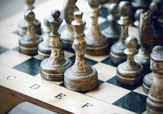 Old chess pieces stand on the chessboard royalty free stock image