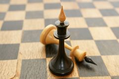 Old chessmen. On the crackled chessboard background Royalty Free Stock Photography