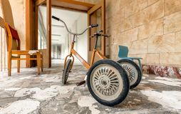 Old kid retro bike in an abandoned nursery Stock Images