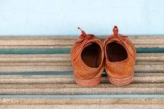 Old children sneakers a wooden background Stock Photos
