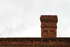 Old Chimney. Old brick chimney on the roof with the sky in the background Stock Image