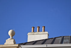 Old chimney pots. Some old style chimney pots on a lead roof with a blue sky background stock image