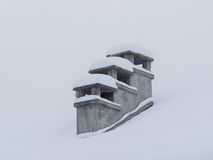 Old chimneys covered by snow in winter during a snowfall Stock Photos