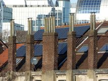 Old chimneys and modern solar panels on house`s roof stock photo