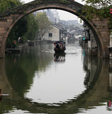 The boat under the stone arch bridge. Bridge and the reflection to form the circular, the houses built beside the river, NANXUN town near Shanghai by UNESCO in Royalty Free Stock Image