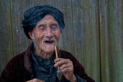 Old chinease man laughing with a pipe Royalty Free Stock Images