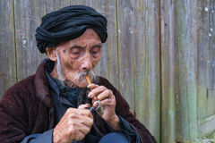 Old chinease man lighting a pipe. Old chinese man lighting a pipe , shot in longji area , china Royalty Free Stock Photography
