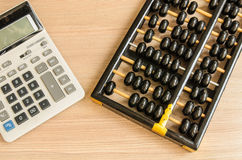 An old chinese abacus and modern calculator Royalty Free Stock Photo
