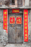 Old Chinese door with peeling fortune posters Stock Images