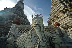 Old Chinese giant statue with Bangkok temple of dawn and blue sky. In a sunny day Royalty Free Stock Photo