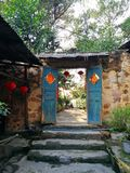 Old Chinese House Gate. Wooden old Chinese house gate is among stone walls in front of the yard of house.Taken in the countryside of Chongqing, China Royalty Free Stock Image
