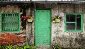 Old Chinese house wall with door and windows. Old Chinese house with green door,green windows and flowers and potted on cement wall Royalty Free Stock Image