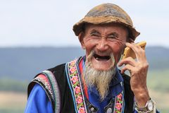 An old chinese man dressed with the traditional attire smoking while enjoying the panorama of DongChuan in Yunnan Province, China. Dongchuan, China - September Royalty Free Stock Photo