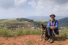 An old chinese man dressed with the traditional attire smoking while enjoying the panorama of DongChuan in Yunnan Province, China. Dongchuan, China - September Royalty Free Stock Image