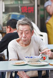 Old Chinese man eats in a neighborhood restaurant, Beijing, China Royalty Free Stock Images