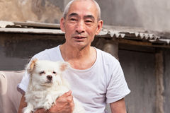 Old Chinese man with his dog. BEIJING – MAY 19, 2011. An old Chinese man with his dog. China's elderly population (60 or older) is about 128 million, one in Royalty Free Stock Photography
