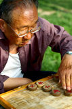 Old Chinese man play Xiangqi.  Royalty Free Stock Photography