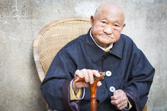 Old Chinese man sitting outdoors with cane Royalty Free Stock Photography