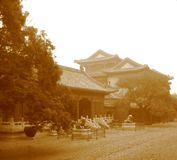 Old Chinese yard. Stylized old-fashioned photo of Chinese pagodas with trees and lion statues Stock Images