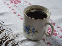 Old chipped cup with painted forget-me-not with black coffee on. Rustic embroider tablecloth Royalty Free Stock Images