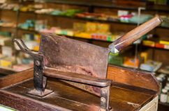 Old chopping knife for cutting a wood of herb in a traditional Chinese pharmacy shop. An Old chopping knife for cutting a wood of herb in a traditional Chinese royalty free stock image