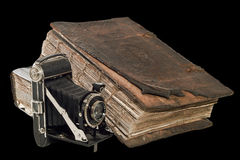 The old Christian Bible near the ancient camera. Isolated on the black Stock Photo