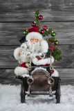 Old christmas decoration: santa claus and an old tin toy car wit Royalty Free Stock Image