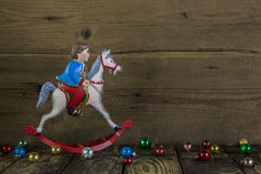 Old christmas decoration of tin: rocking horse on wooden backgro Stock Photos