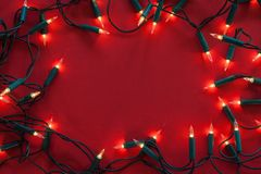 Old christmas decorative lights on red background. Old christmas decorative lights on red surface with dimmed shine - framing copy space in center stock photos