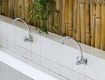 Old chrome faucet. Of the row basik near the bamboo wall.select focus Stock Photo