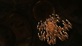 Old Chrystal chandeliers with ambient light in the darkness close up.  stock video footage