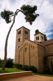 Old church. Massive old brick church in simple architectural style near a pine tree, Spanish Village, Barcelona, Spain Royalty Free Stock Image