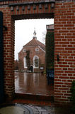 Old Church. A view of an old church through a passage in between a red brick wall, in a small German town stock image