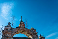 Old Church archway, overgrown with birches, Russia. Old Church arch of red brick, overgrown with birches on a background blue sky, Russia Royalty Free Stock Photography