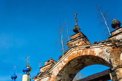 Old Church archway, overgrown with birches, Russia. Old Church arch of red brick, overgrown with birches on a background blue sky, Russia Royalty Free Stock Image