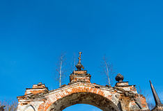 Old Church archway, overgrown with birches, Russia. Old Church arch of red brick, overgrown with birches on a background blue sky, Russia Stock Image