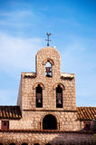 Old church bell tower. One of old beautiful chapel bell towers in Spanish village with a cook on its spire, Barcelona, Spain Royalty Free Stock Photography