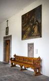 Old Church bench. Under an old painting in a monastery hallway Stock Image