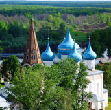 Old Church with blue domes on the background of the forest to the plains leaving behind the horizon Stock Photos