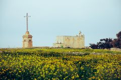 Old Church and cross in the field. Church and big cross in the field of yellow flowers Royalty Free Stock Photos